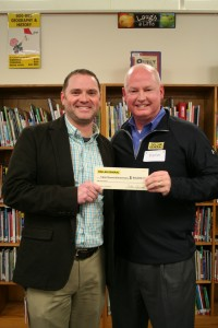 Dollar General's Mark Flowers is presenting a $50,000 check to principal Matthew Hull